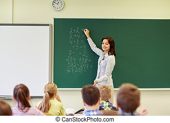 school kids and teacher writing on chalkboard - education,...