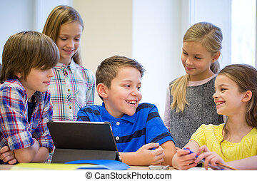 group of school kids with tablet pc in classroom -...
