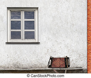 accordion on the bench near the wall with a window...