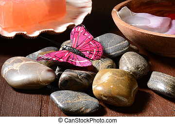 Spa setting - A butterfly rests on zen stones in a spa...