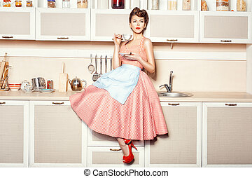 Girl in apron - Woman in an apron in the kitchen drinking...