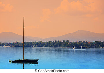 boats on a calm lake surface at sunset