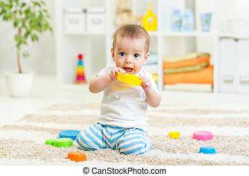 baby boy playing with toys indoors at home