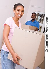 man and woman relocating - a man and woman moving boxes...
