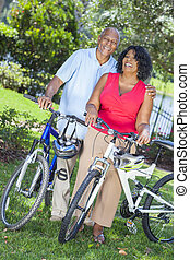 Senior African American Woman and Man Couple Riding Bikes -...