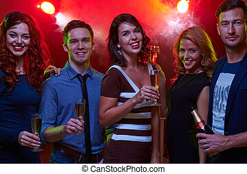Night entertainment - Group of friendly guys and girls with...