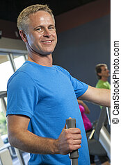 Middle Aged Man Running on Gym Exercise Machine - Middle...