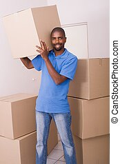 african man carrying boxes and smiling