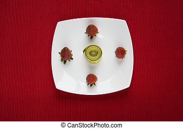 Strawberry in a plate over a red background