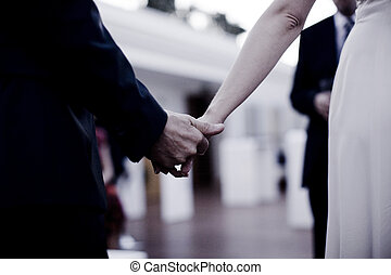 Bride and groom in wedding ceremony holding hands - Bride...