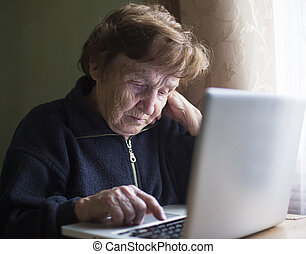 Old woman with a laptop at home.