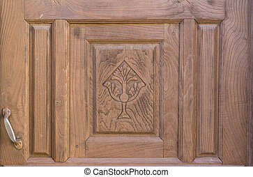 Old brown run-down religious decorated wooden door -...