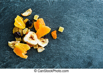 Closeup on mix of dried fruits on stone substrate