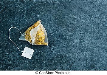 Closeup on camomile tea bag on stone substrate