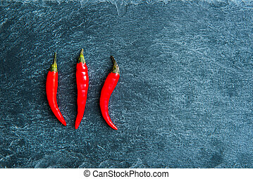 Closeup on red chili peppers on stone substrate