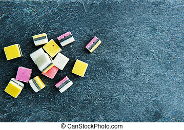 Closeup on liquorice candies on stone substrate