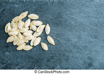 Closeup on pumpkin seeds on stone substrate
