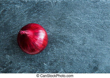 Closeup on red onion on stone substrate