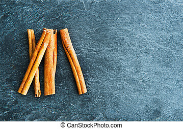 Closeup on cinnamon sticks on stone substrate