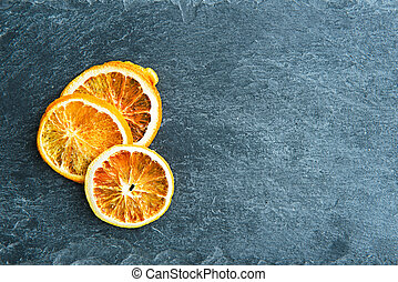 Closeup on dried orange slices on stone substrate