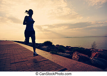 woman runner athlete running at sunrise seaside