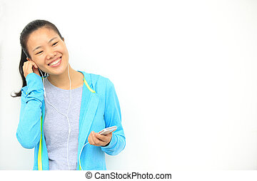 young woman listening music - happy beautiful young asian...