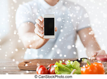 close up of man showing smartphone in kitchen - cooking,...