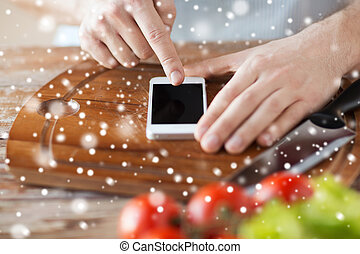 close up of man reading recipe from smartphone - cooking,...