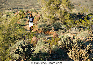 Desert Trail Hike - Young man hiking outdoors on a trail at...