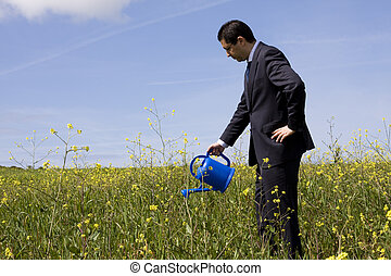businessman with a flowerpot - businessman at the field with...