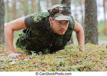 young soldier or ranger doing push-ups in forest - war,...