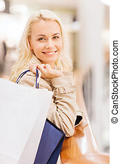 happy young woman with shopping bags in mall - sale,...