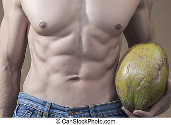 Coconut and abs - Closeup of muscular lean torso of...