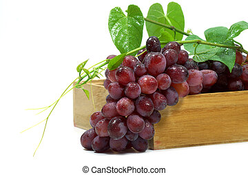 Red grape in wood box on white background.