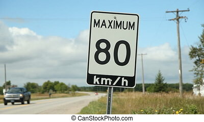 Maximum 80 km/hr sign with cars. - Traffic passing a maximum...