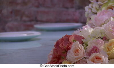 Bouquet of flowers on table against brick wall - Bouquet of...