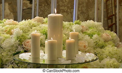 Close-up of lighted candles on flowers background - View of...