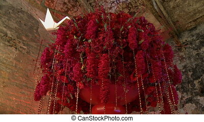 Huge pot with red flowers hang from ceiling - View of huge...