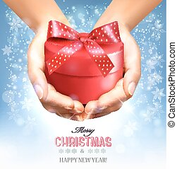 Holiday christmas background with hands holding gift box....