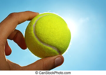 Hand holding tennis ball up to the sky