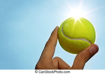 Hand holding tennis ball up to sky - A mans hand holding a...