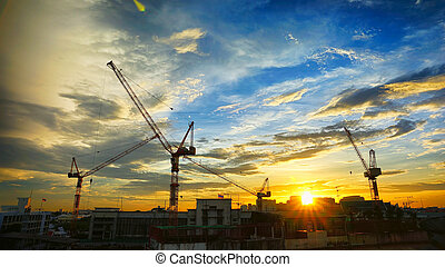 Industrial landscape with silhouettes of cranes on the...