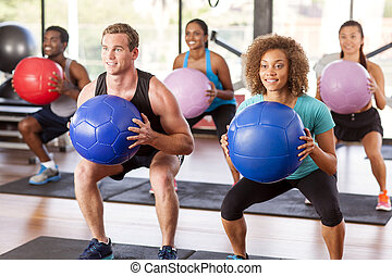 Gym class doing squats - Multi-ethnic gym class doing squats...