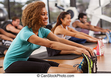Young woman stretching in a gym - Young mixed-race woman...