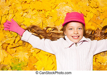 Happy smiling girl on autumn leaves - Close portrait of...