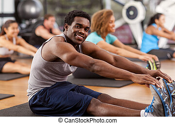 Young African-American man stretching in a gym and looking...