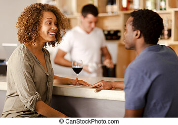 Couple talking in a bar - Young mixed-race couple talking in...
