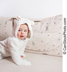 1 year old baby boy dressed in bunny overall at home