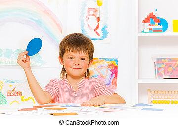 Happy little boy learning shapes in kindergarten