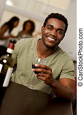 African-American man holiding a wine glass in a restaurant -...